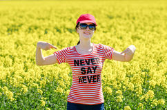 Beautiful female in red cap and t-shirt with Never say never text. Woman is smiling and showing you a phrase. Girl are royalty free stock images