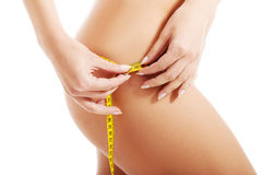 Beautiful female's thigh with measuring tape. Stock Photo