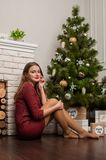 Beautiful female in Santa Hat near Christmas tree and present boxes stock photo