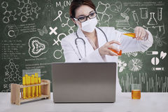 Beautiful female scientist pour liquid with written chalkboard Royalty Free Stock Image