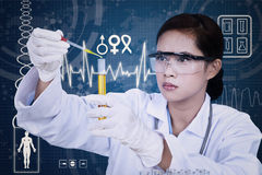 Beautiful female scientist using pipette on digital background. Beautiful female scientist using pipette on blue digital background Stock Photo