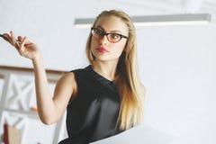 Beautiful female secretary portrait. Portrait of beautiful female secretary with glasses and document in hand. Blurry office background. Work, job, occupation Royalty Free Stock Photo