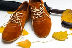 Beautiful women shoes. Beautiful female shoes on laces on a white background and autumn leaves with umbrella royalty free stock images