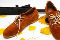 Beautiful women shoes. Beautiful female shoes on laces on a white background and autumn leaves with umbrella royalty free stock image