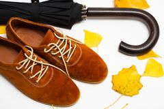 Beautiful women shoes. Beautiful female shoes on laces on a white background and autumn leaves with umbrella royalty free stock photos
