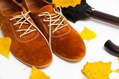 Beautiful women shoes. Beautiful female shoes on laces on a white background and autumn leaves with umbrella stock images