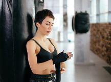 Beautiful female with short black hair putting on straps while work out. At sport club. being ready for fight Royalty Free Stock Images