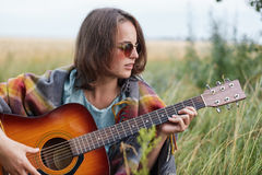 Beautiful female with short hairstyle wearing stylish sunglasses resting outdoors playing guitar enjoying her summer vacations. Fe. Male musician in stylish Stock Photo