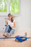 Beautiful female sitting on floor. loking in clipboard and think Stock Photo