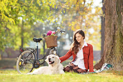 Beautiful female sitting on a grass with her dog in a park Stock Photography