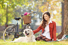 Beautiful female sitting on a grass with her dog in a park Stock Photos