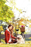 Beautiful female sitting on a grass and looking at her dog in a Stock Photography
