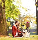Beautiful female sitting on grass and looking at her labrador re Royalty Free Stock Photography