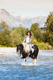Beautiful Female sitting on horse while crossing r Royalty Free Stock Image