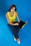 Beautiful female sitting with a laptop Royalty Free Stock Photography