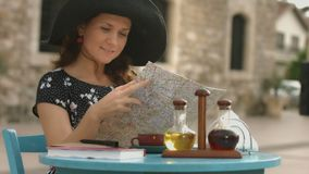 Beautiful female sitting at street cafe table with luggage, examining city map. Stock footage stock video