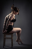 Beautiful female slave sitting bondage ropes on chair. Isolated on gray background Royalty Free Stock Photography