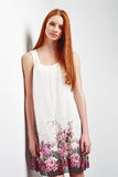 Beautiful female in sleeveless flower print summer dress. Tender portrait of beautiful redhead female wearing sleeveless flower print summer dress posing leaning Royalty Free Stock Photo
