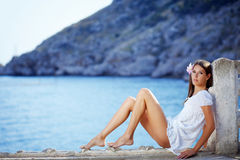 Beautiful female with slim legs posing over sea Royalty Free Stock Photos