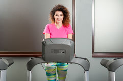 Beautiful female smiling and exercising on treadmill Royalty Free Stock Photography