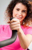 Beautiful female smiling and holding a stationary bike handle Royalty Free Stock Photography