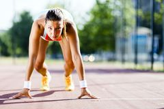 Female sprinter getting ready for the run. Beautiful female sprinter getting ready for the run during summer Royalty Free Stock Images