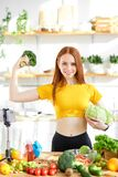 beautiful female stand holding cabbage and broccoli in hands, lead heathy lifestyle and eating