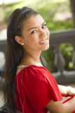 Beautiful female student. A smiling student outdoors, looking over at camera Royalty Free Stock Photo