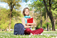 Beautiful female student with book and headphones sitting on a g Royalty Free Stock Photography