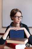 Beautiful female student with books. Beautiful female student with glasses folded her hands on the books in the classroom Stock Photo
