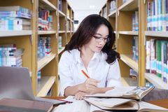Beautiful female student doing schoolwork in library. Portrait of beautiful female student wearing glasses while studying in the library Stock Photo