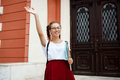 Beautiful female student in glasses smiling, greeting, holding folders outdoors. Stock Photos