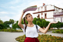 Beautiful female student  holding folders above head, hiding from rain. Royalty Free Stock Image