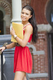 Beautiful female student holding a notebook. A beautiful student clutches a folder. Shot outdoors with natural light Stock Photography