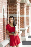Beautiful female student leaning against a brick w Stock Image