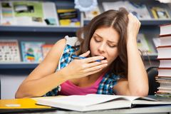 Beautiful female student in a library. Beautiful female student in a university library Royalty Free Stock Photos