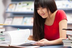 Beautiful female student in a library Royalty Free Stock Photos