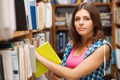 Beautiful female student in a library. Beautiful female student in a university library Stock Photography