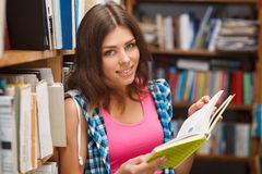 Beautiful female student in a library. Beautiful female student in a university library Stock Photo