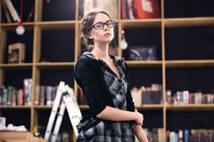 Beautiful female student in a library. Beautiful female student with glasses in a library Royalty Free Stock Images