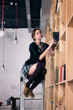 Beautiful female student in a library. Beautiful female student on stairs puts books in the library Stock Photos