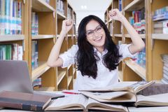 Beautiful female student lifting her hands in library. Beautiful female student looks happy while lifting her hands and sitting in the library Royalty Free Stock Photos