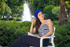 Beautiful female student is reading a book outdoors. Royalty Free Stock Images