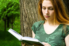 Beautiful female student reading in campus. Portrait of beautiful female student reading in campus Stock Images