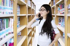 Beautiful female student speaking on the phone. Portrait of beautiful female student speaking on the mobile phone while standing in the library Stock Photo