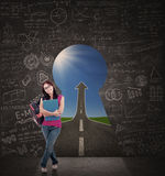 Beautiful female student standing in front of keyhole of success Stock Photos
