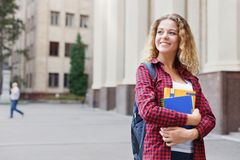 Beautiful female student standing in front of the university campus Stock Image