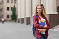 Beautiful female student standing in front of the university campus Royalty Free Stock Image