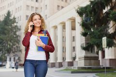Beautiful female student standing in front of the university campus Royalty Free Stock Photo
