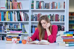 Beautiful female student in a university library. Group of students learning in library at university stock photo
